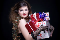 Closeup portrait of girl with some presents. Closeup portrait of beautiful girl with red lips, tinsel and present on black Stock Images