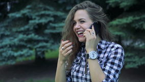 Closeup portrait of girl speaking on the phone on green trees background. Slowly stock footage