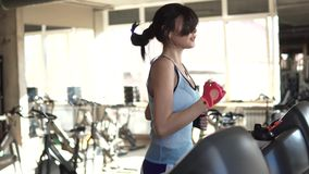 Closeup portrait of a girl on the treadmill in the gym. Girl running on the treadmill in the fitness room. young woman doing aerobic exercises. Exercising in the stock footage