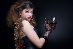 Closeup portrait of girl with wineglass on. Closeup portrait of beautiful girl in black gloves with red lips, tinsel and wineglass on black Stock Photo