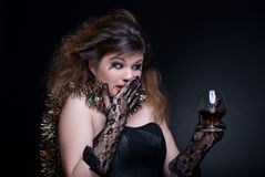 Closeup portrait of girl with wineglass. Closeup portrait of beautiful girl in black gloves with red lips, tinsel and wineglass on black Royalty Free Stock Image