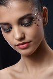 Closeup portrait of glittering makeup. Closeup facial portrait of attractive young woman wearing elegant glittering makeup with strasses, eyes closed Stock Photography