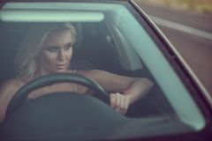 Closeup portrait of gorgeous sexy tanned blond lady driving the. Car and looking into wing mirror Royalty Free Stock Photography
