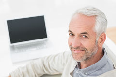 Closeup portrait of a grey haired man with laptop Stock Photo
