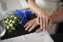 Closeup portrait of groom holding brides hand on table near bouquet Stock Image