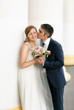 Closeup portrait of groom kissing bride in cheek at high columns Royalty Free Stock Image