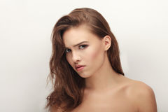 Closeup portrait of grumpy young cute playful brunette woman posing with bare shoulders against white studio background Stock Photos
