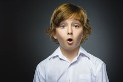 Closeup Portrait of handsome boy with astonished expression while standing against grey background Royalty Free Stock Images