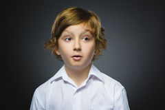 Closeup Portrait of handsome boy with astonished expression while standing against grey background Stock Photos