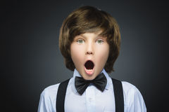 Closeup Portrait of handsome boy with astonished expression while standing against grey background Stock Images