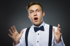 Closeup Portrait of handsome boy with astonished expression while standing against grey background Stock Photo