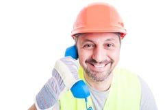 Closeup portrait of handsome builder talking on telephone. Closeup portrait of cheerful handsome builder talking on telephone  on white Stock Photo