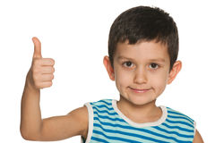 Closeup portrait of a boy holds his thumb up Royalty Free Stock Photography
