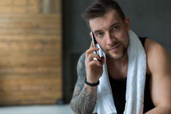 Closeup portrait of handsome man call mobile phone in gym Stock Photography