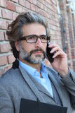 Closeup portrait of handsome man having serious conversation on cell phone outside.  Royalty Free Stock Image