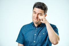 Closeup portrait of handsome man putting hand up to face and fak Royalty Free Stock Photography