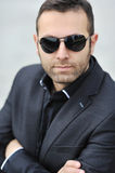Closeup portrait of handsome man's face wearing sunglasses - out Stock Image