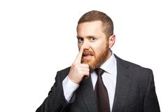 Closeup portrait of handsome serious businessman with facial beard in black suit standing and touching his nose and showing lie. Gesture. indoor studio shot royalty free stock photo