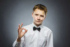 Closeup Portrait of handsome teenager smiling and show Ok over grey background royalty free stock image