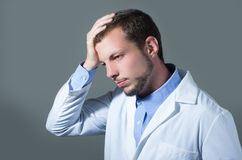 Closeup portrait of handsome worried young doctor Stock Photos