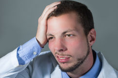 Closeup portrait of handsome young confused doctor Stock Photography