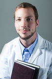 Closeup portrait of handsome young doctor holding Royalty Free Stock Photo