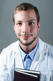 Closeup portrait of handsome young doctor holding Royalty Free Stock Images