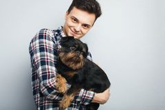 Closeup portrait handsome young hipster man, kissing his good friend black dog isolated light background. Positive human emotions, stock images
