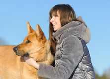 Portrait handsome young woman, kissing her good friend dog on bl. Closeup portrait handsome young hipster woman, kissing her good friend dog on blue sky Stock Images
