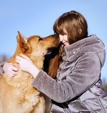 Portrait handsome young woman, kissing her good friend dog on bl. Closeup portrait handsome young hipster woman, kissing her good friend dog on blue sky Royalty Free Stock Photography