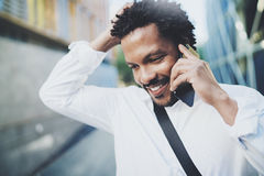 Closeup portrait of happy American African man using smartphone to call friends at sunny street.Concept of happy young Royalty Free Stock Images