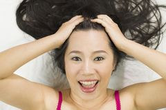 Closeup portrait of happy asian women  lying on ground with black long hair. acting smile, fun stock photo