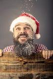 Closeup portrait of a happy bearded man with santa cap looking u royalty free stock image