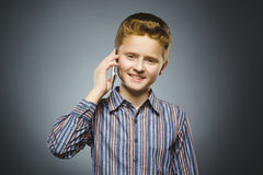Closeup Portrait of happy boy with mobile or cell phone on gray background Stock Photo