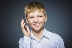 Closeup Portrait of happy boy with mobile or cell phone on gray background Stock Photos