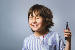 Closeup Portrait of happy boy with mobile going surprise on gray background Stock Photo