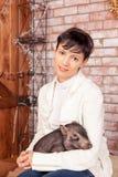 Closeup portrait, happy, brunette woman, bank employee, hugging black piggy, Chinese New Year Symbol, isolated on brick stock photo