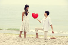 Closeup portrait of happy couple at the beach with heart. Royalty Free Stock Photo