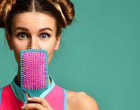 Closeup portrait of happy fashion brunette woman close mouth with colorful pink blue yellow big hair comb brush stock image