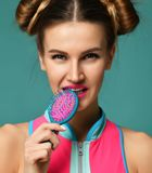 Closeup portrait of happy fashion brunette woman close mouth with colorful pink blue yellow big hair comb brush stock photography