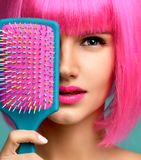 Closeup portrait of happy fashion brunette woman close mouth with colorful pink blue yellow small hair comb brush in pink wig stock image