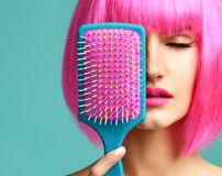 Closeup portrait of happy fashion brunette woman close mouth with colorful pink blue yellow small hair comb brush in pink wig stock photos