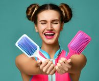 Closeup portrait of happy fashion brunette woman with colorful pink and white blue big square hair comb brushes screaming royalty free stock photography