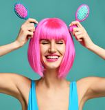 Closeup portrait of happy fashion brunette woman hold two small pink blue small hair comb brush in pink wig royalty free stock photos