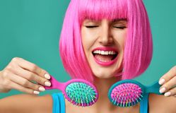Closeup portrait of happy fashion brunette woman hold two small pink blue small hair comb brush in pink wig stock image