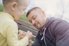 Closeup portrait of a happy father and son playing on playground. And having fun. Young father playing with his baby outside in park. Dad and son royalty free stock images