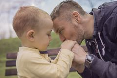 Closeup portrait of a happy father and son playing on playground. And having fun. Young father playing with his baby outside in park. Dad and son stock photo