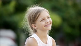 Closeup portrait of happy girl. In elementary school age outdoors stock video