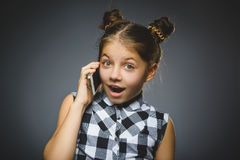 Closeup Portrait of happy girl with mobile or cell phone on gray background Royalty Free Stock Photography