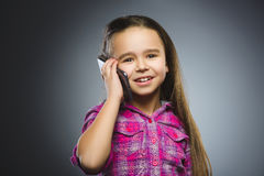 Closeup Portrait of happy girl with mobile or cell phone on gray background Stock Images